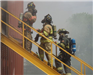 Firefighters on stairs surrounded by smoke