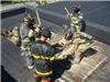 Firefighters on roof using tools