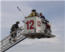 Firefighters on extended ladder