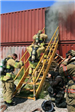 Firefighters climbing stairs to burning building