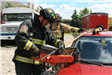 Firefighter using cutting tool on car