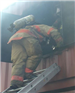Firefighter climbing into burning building