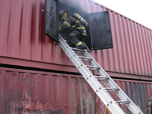 Firefighter climbing into window from ladder