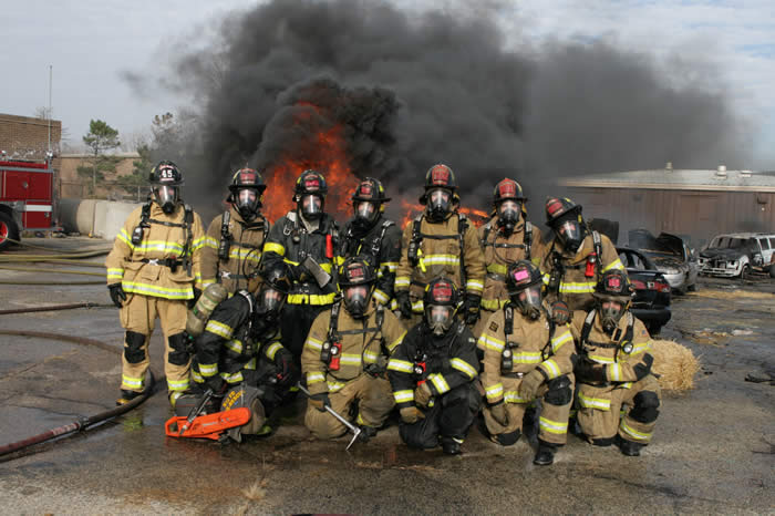 Firefighters in full gear posing in front of fire